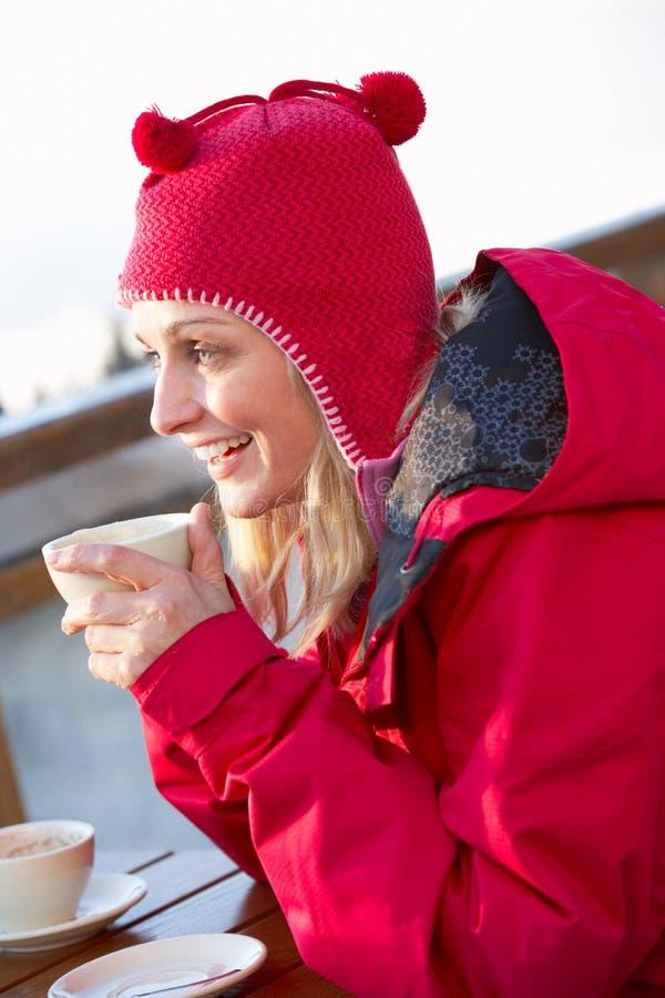 Kvinnan som tycker om den varma drinken i Cafe på, skidar semesterorten royaltyfri foto
