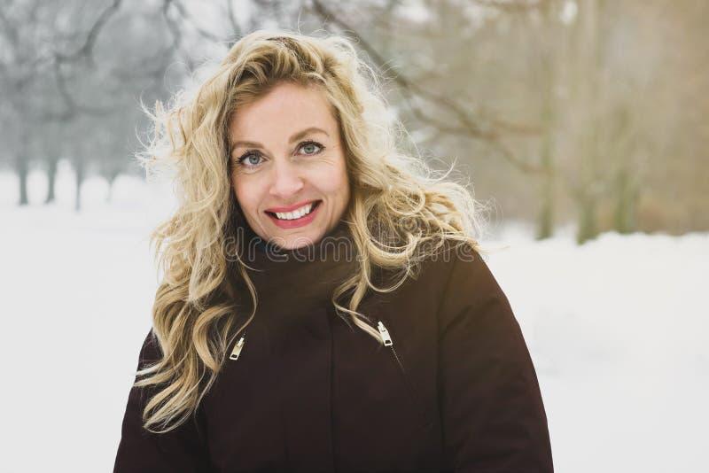 Kvinnan som tycker om en vinter, går till och med täckt snö parkerar royaltyfria foton