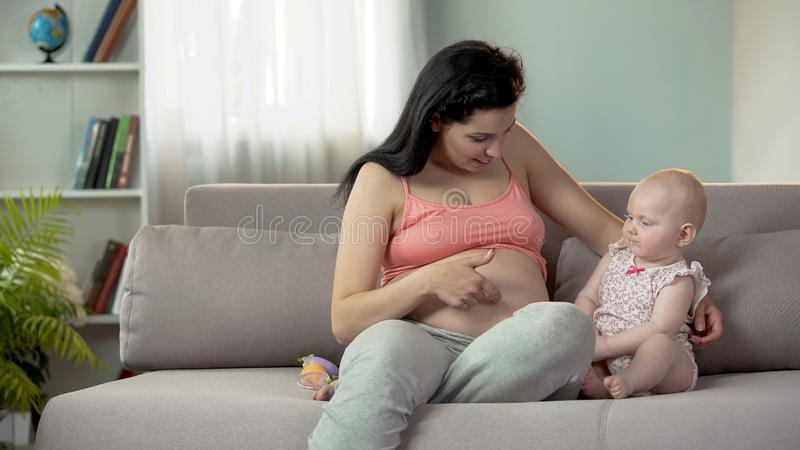 Kvinnan som tycker om havandeskap, trycker på hennes stora buk och berättar, behandla som ett barn om syster royaltyfri fotografi