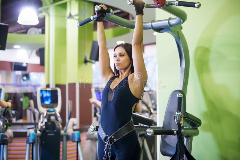 Kvinnan som utför handtag, ups i en stång på idrottshallen royaltyfri bild
