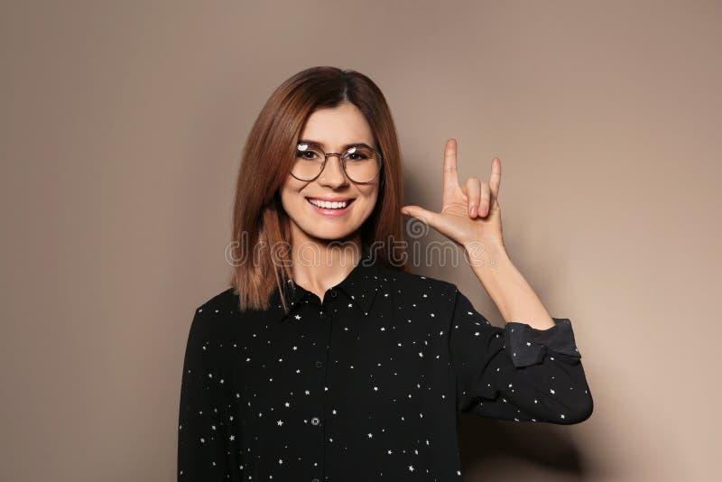 Kvinnan som visar ÄLSKAR JAG, DIG gesten i teckenspråk royaltyfri foto