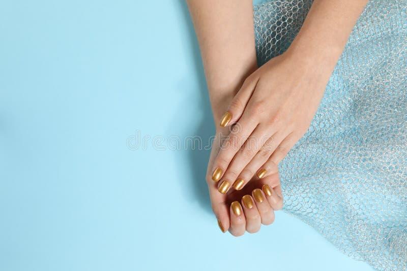 Kvinnan som visar manicured händer med guld-, spikar polermedel på färgbakgrund, bästa sikt royaltyfri foto