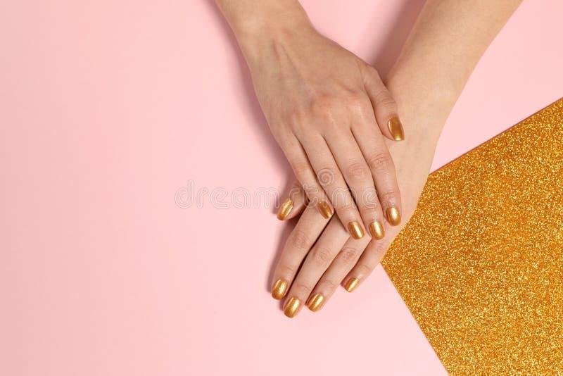 Kvinnan som visar manicured händer med guld-, spikar polermedel på färgbakgrund, bästa sikt arkivfoto