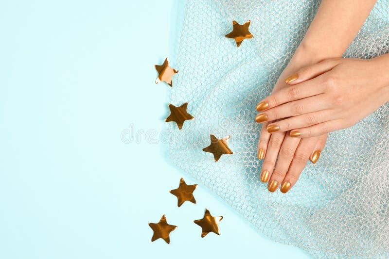 Kvinnan som visar manicured händer med guld-, spikar polermedel på färgbakgrund, bästa sikt royaltyfri fotografi