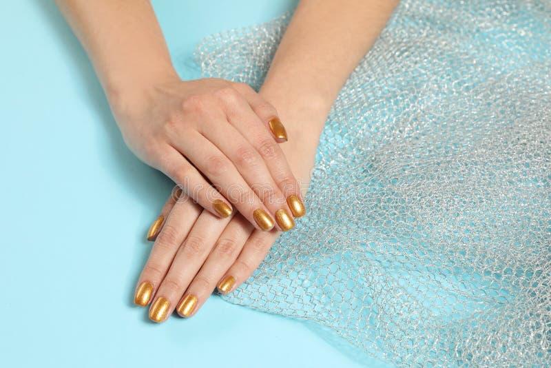 Kvinnan som visar manicured händer med guld-, spikar polermedel på färgbakgrund Utrymme f?r text arkivbild