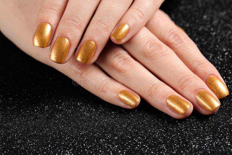 Kvinnan som visar manicured händer med guld-, spikar polermedel på svart bakgrund arkivbilder