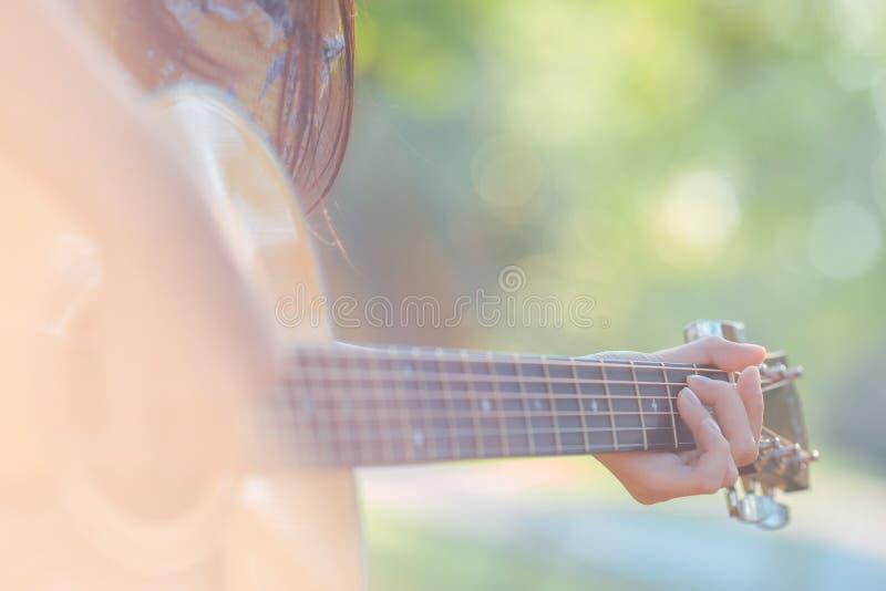 Kvinnan spelar den akustiska gitarren i trädgården arkivfoto