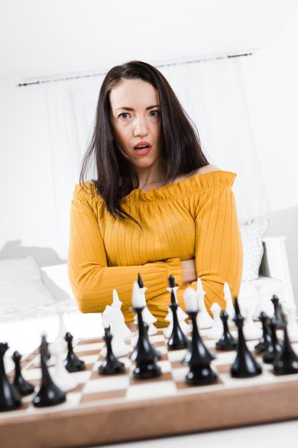 Kvinnan spelar schack och visar överraskningansiktsuttryck arkivbild