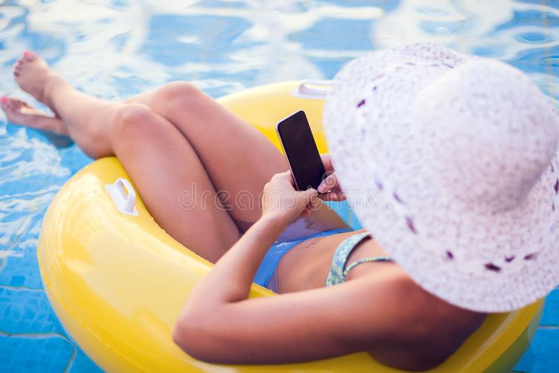 Kvinnan spenderar tid och har att koppla av på pölen med telefonen Folk-, sommar- och feriebegrepp arkivfoton