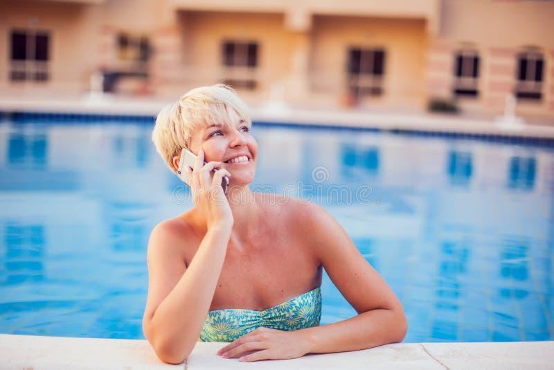 Kvinnan spenderar tid och har att koppla av på pölen med telefonen Folk-, sommar- och feriebegrepp arkivbild