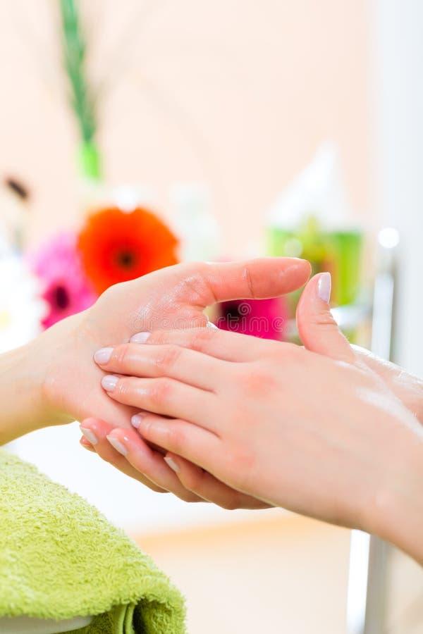Kvinnan spikar in massage för salonghälerihand arkivfoto