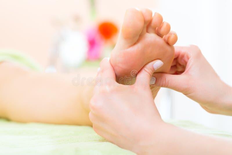 Kvinnan spikar in salongen som mottar fotmassage royaltyfri bild