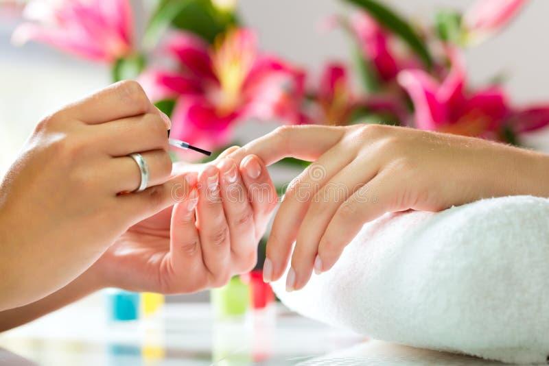 Kvinnan spikar in salongen som mottar manicuren royaltyfri foto