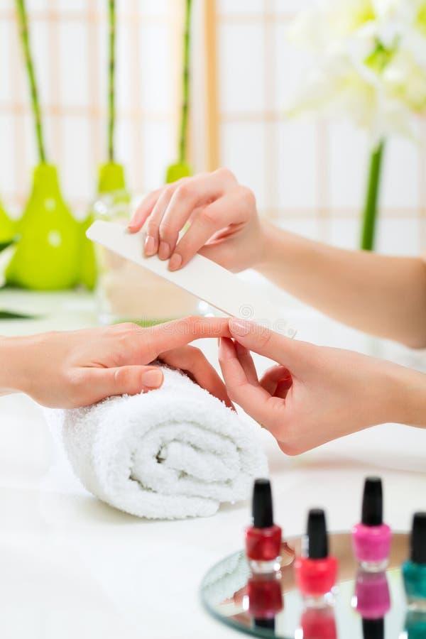 Kvinnan spikar in salonghälerimanikyr royaltyfri foto