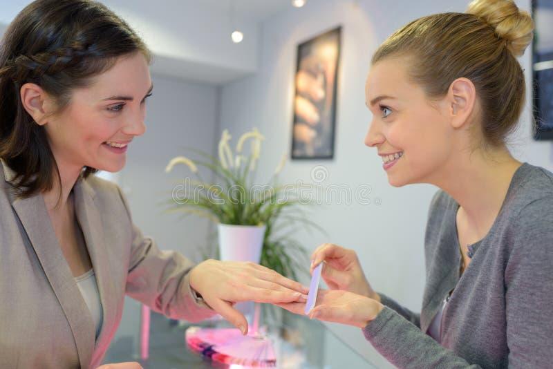 Kvinnan spikar in salonghälerimanikyr av kosmetologen arkivfoto