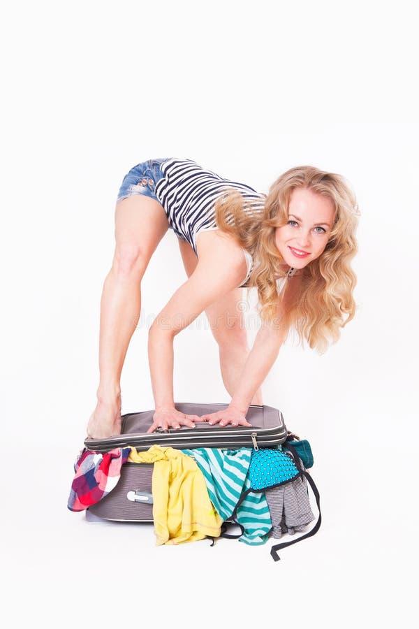 Kvinnan stänger en resväska mycket av kläder royaltyfri foto
