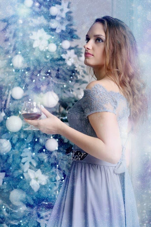 Kvinnan står med ett exponeringsglas av konjak royaltyfri bild
