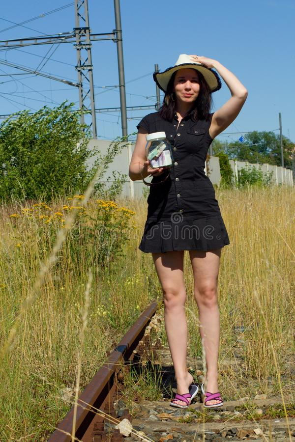 Kvinnan står på bevuxna spår, rymmer ett exponeringsglas fullt av pengar i hennes hand och väntar på ett drev fotografering för bildbyråer