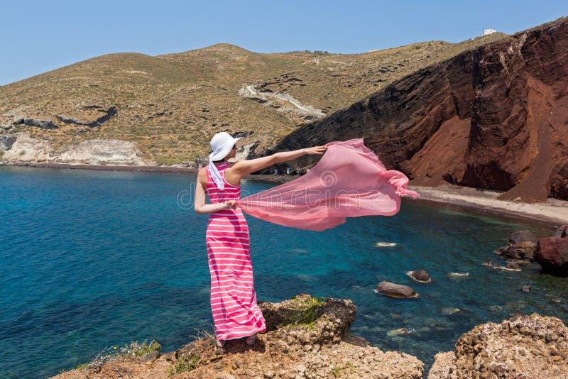 Kvinnan står på en klippa och ser den röda stranden royaltyfri bild