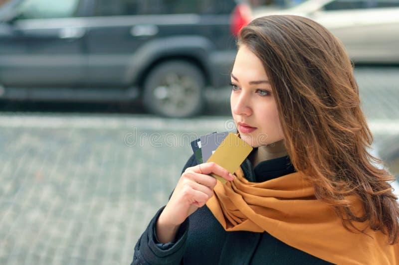 Kvinnan står på en stadsgata med en kreditkort arkivbilder
