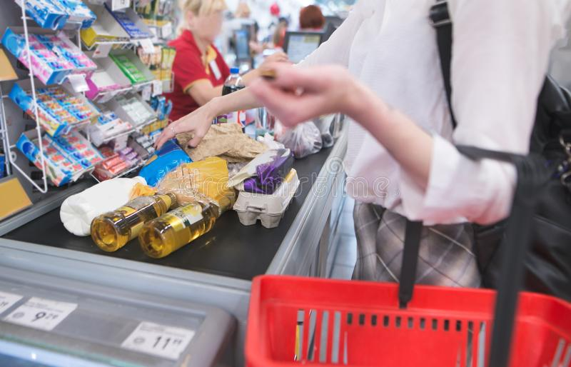 Kvinnan står på supermarket och väntar på en kö Gör köp i lagret arkivbild