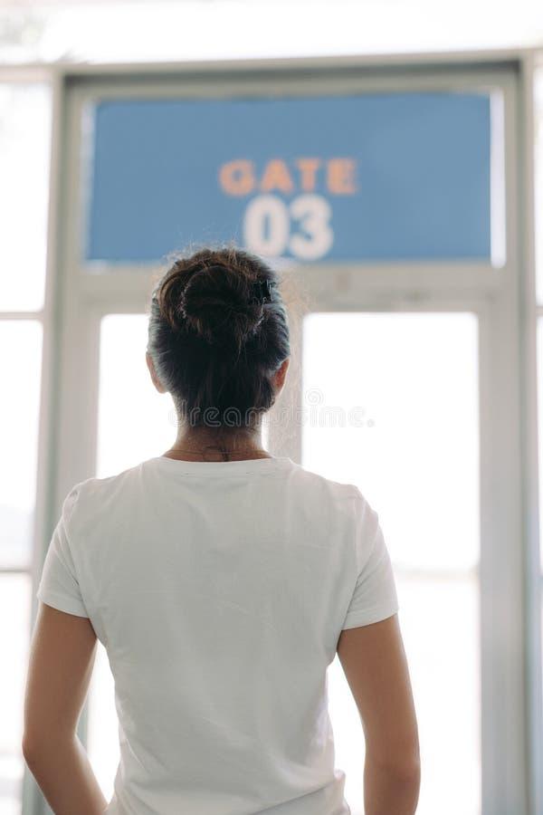 Kvinnan st?r framme av porten i en flygplats royaltyfri foto