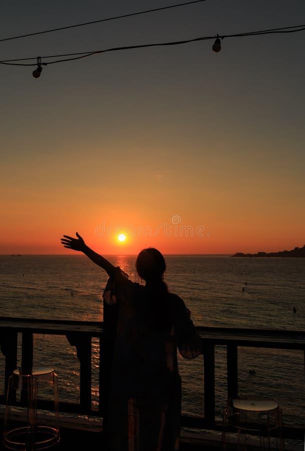 kvinnan sträcker hennes hand för att gripa solen royaltyfria bilder