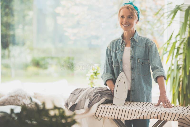 Kvinnan stryker kläder royaltyfri foto