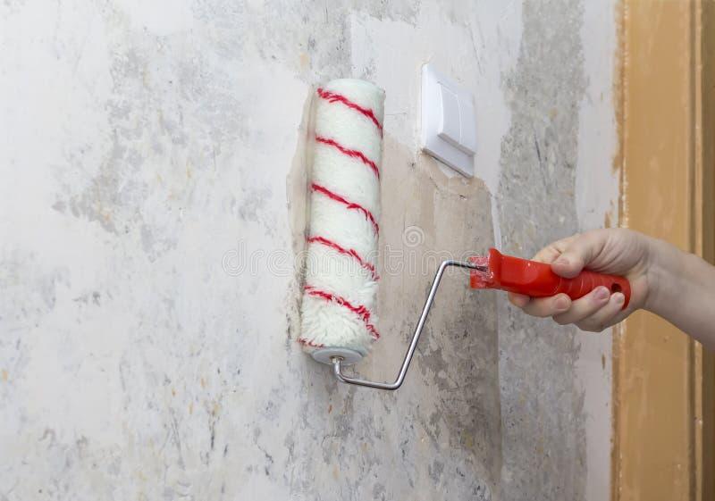 Kvinnan suddar lim på väggen under tapeten royaltyfria foton