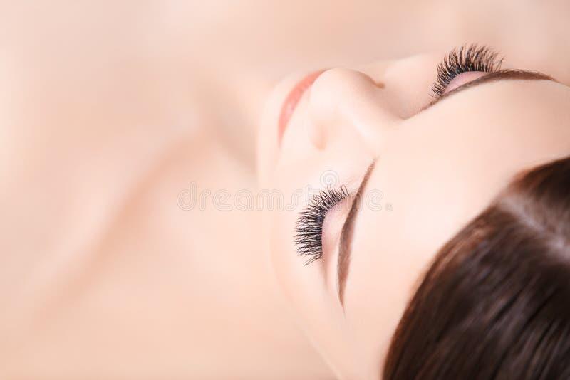 Kvinnan synar med långa ögonfranser Ögonfransförlängning royaltyfri bild