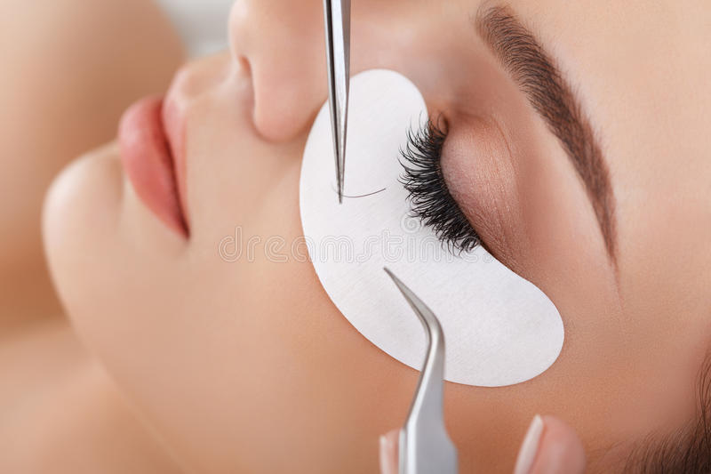 Kvinnan synar med långa ögonfranser Ögonfransförlängning arkivfoton