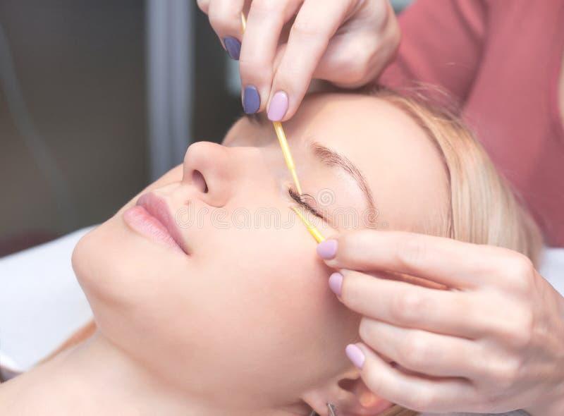 Kvinnan synar med långa ögonfranser Ögonfransförlängning fotografering för bildbyråer