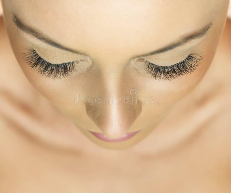 Kvinnan synar med långa ögonfranser Ögonfransförlängning - rysk volym snärtar arkivbilder