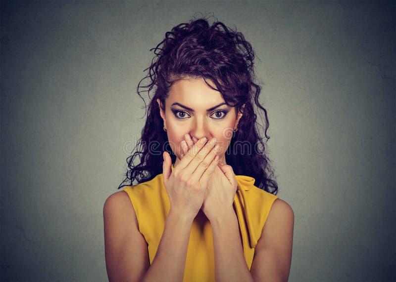 Kvinnan täcker hennes mun med händer arkivbild