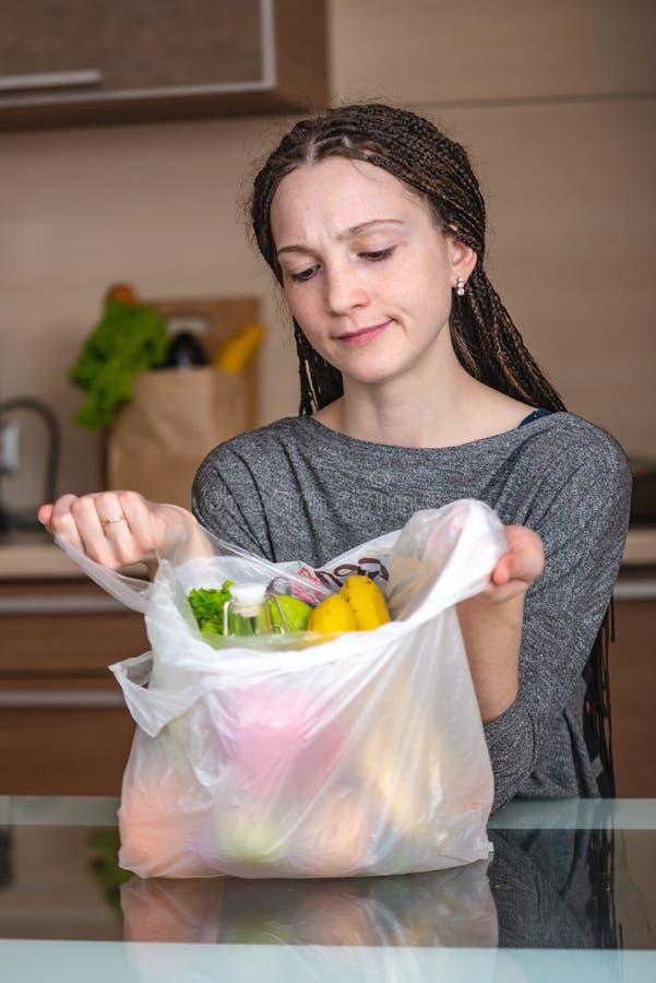 Kvinnan tänker det för att vägra att använda en plastpåse för att köpa produkter r arkivfoto