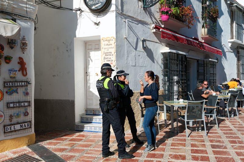 Kvinnan talar med poliser på gatan av den gamla staden arkivbilder