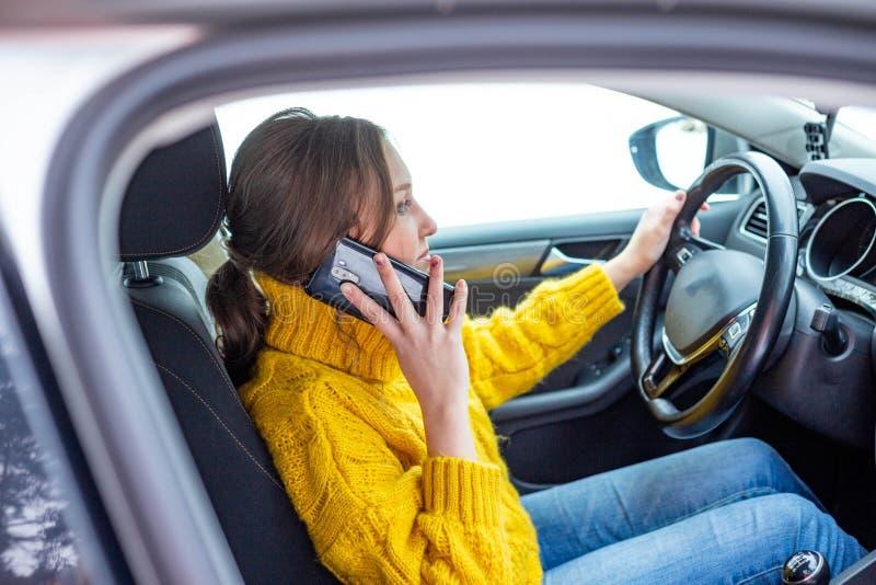 Kvinnan talar på hennes telefon, medan köra en bil fotografering för bildbyråer
