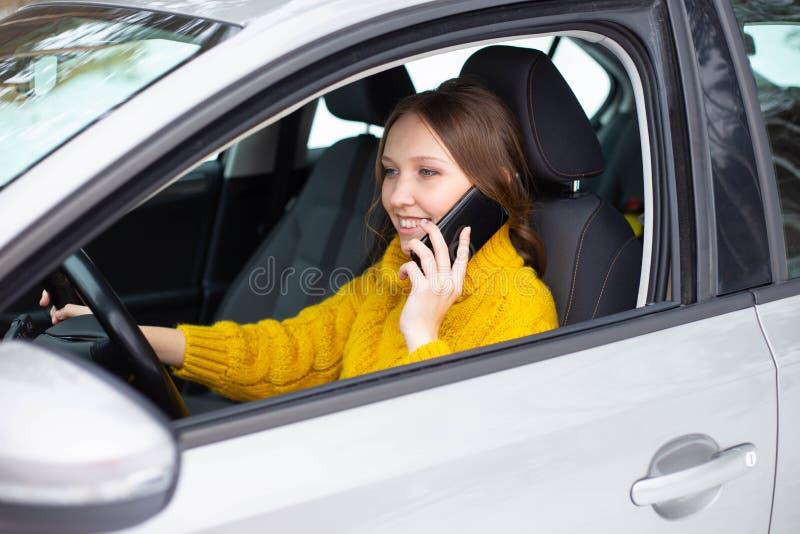 Kvinnan talar p? hennes telefon, medan k?ra en bil arkivfoton
