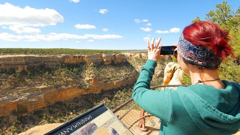 Kvinnan tar bilden av Cliff Dwellings With Smartphone fotografering för bildbyråer