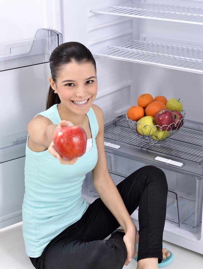 Kvinnan tar det röda äpplet från kylen royaltyfri fotografi