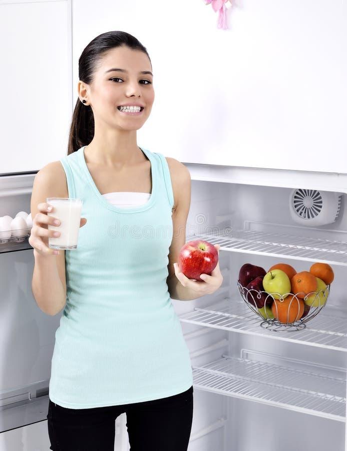 Kvinnan tar det röda äpplet och mjölkar från kylen fotografering för bildbyråer