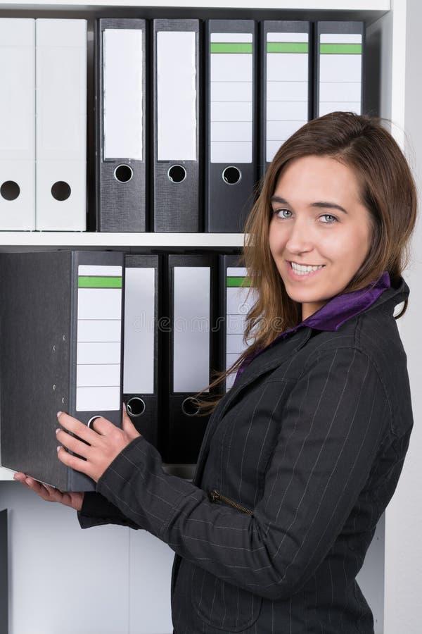 Kvinnan tar en mapp ut ur en hylla royaltyfria bilder