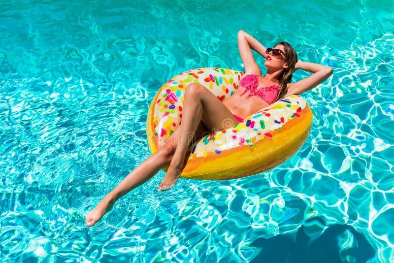 Kvinnan tar en sunbath i munken formad pölflöte på en varm sommardag royaltyfri fotografi