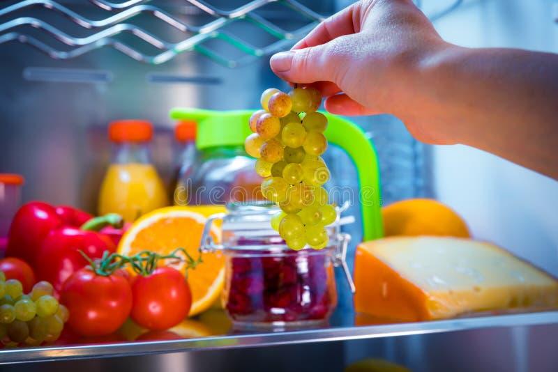 Kvinnan tar gruppen av druvor från det öppna kylskåpet arkivfoton