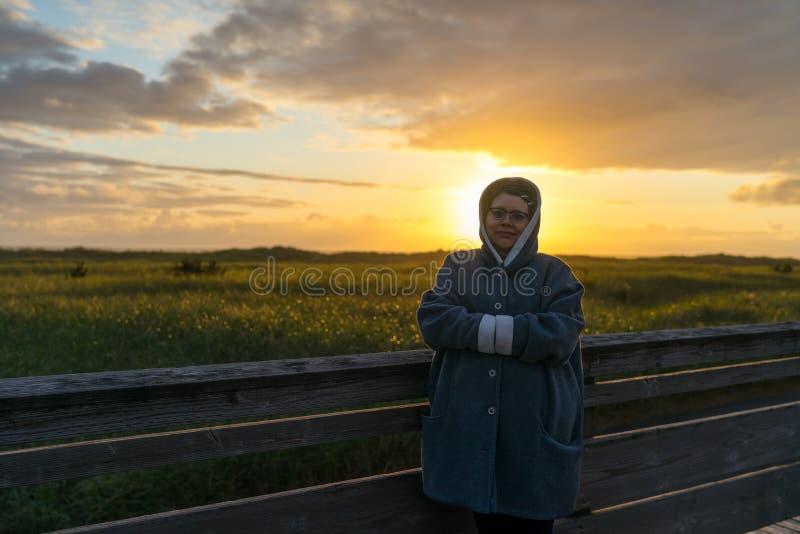 Kvinnan tar i flyktigt solnedgångögonblick royaltyfri bild