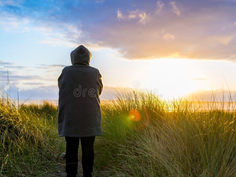 Kvinnan tar i flyktigt solnedgångögonblick arkivbilder