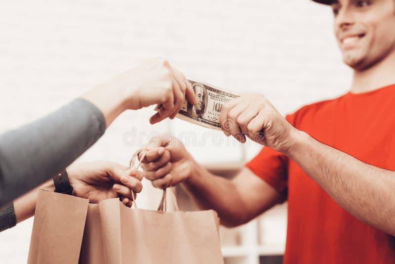 Kvinnan tar packen från kurir och ger kassa royaltyfri bild