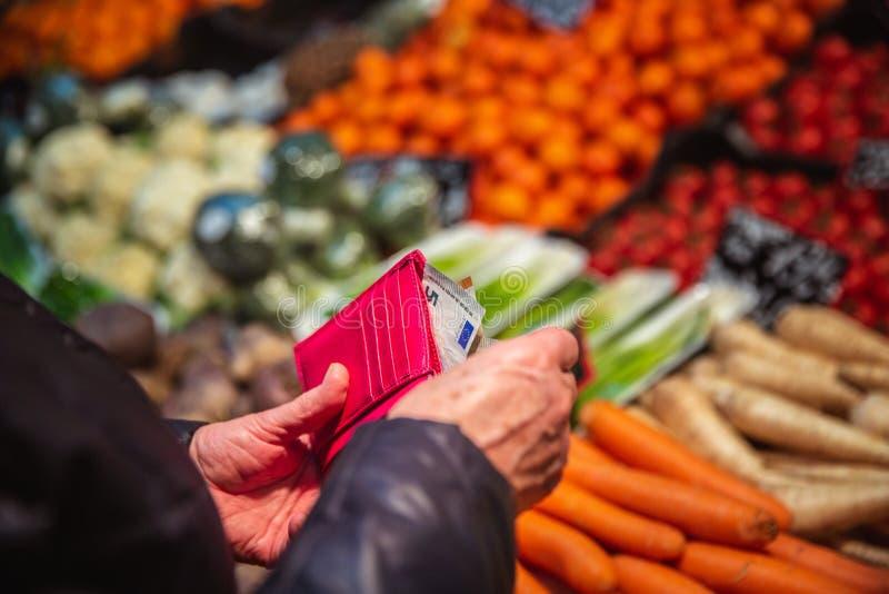 Kvinnan tar pengar ut från plånboken på marknad arkivfoton