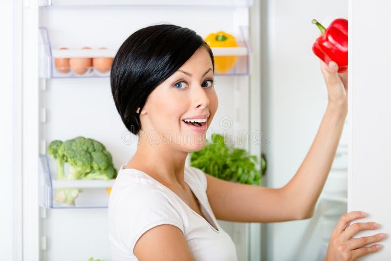 Kvinnan tar röd peppar från den öppnade kylen royaltyfria bilder