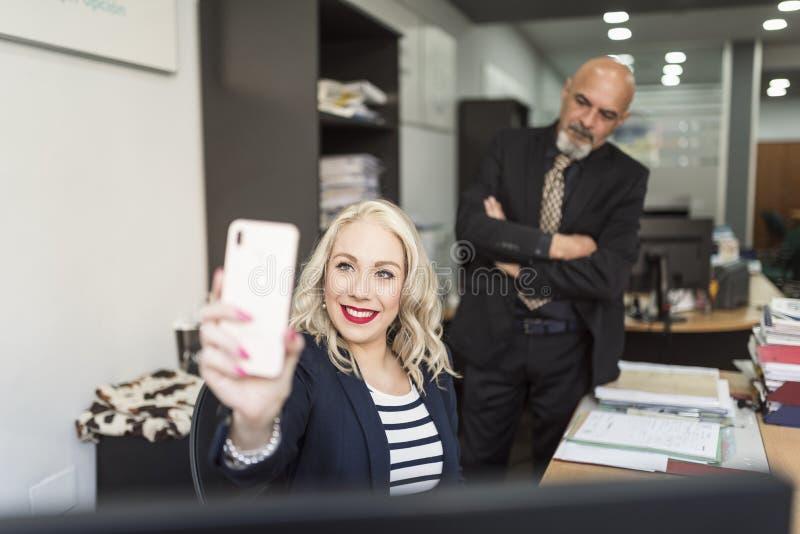 Kvinnan tar selfie med telefonen, medan förvånas av framstickandet som är bak hennes ilsket arkivfoton